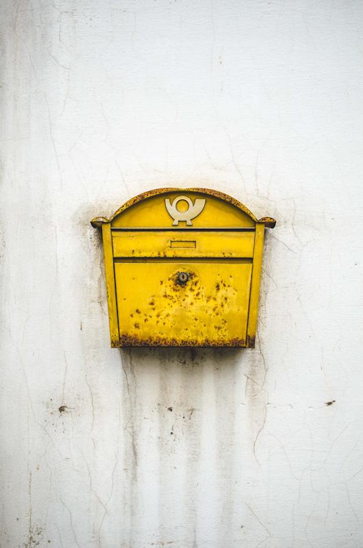 Ein Briefkasten hängt an einer grauen Hauswand