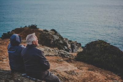Zwei Menschen sitzen auf einer Bank und schauen aufs Meer hinaus