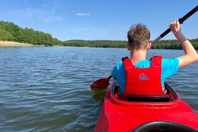Ein Kind paddelt im Kanu über einen See