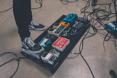 Eine Person stellt ein Gitarrenpedal ein