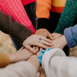 Im Kreis stehende Personen fassen sich an der Hand